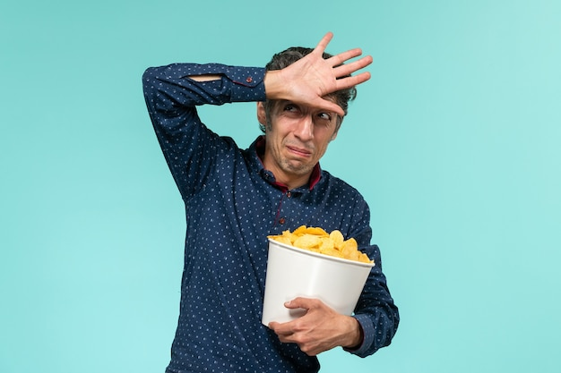 Мужчина средних лет, вид спереди, держит корзину с чипсами и смотрит фильм на синем столе