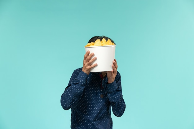 Front view middle-aged male holding basket with cips on blue surface