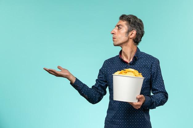 Cestino maschio di mezza età della holding di vista frontale con le patatine fritte sullo scrittorio blu