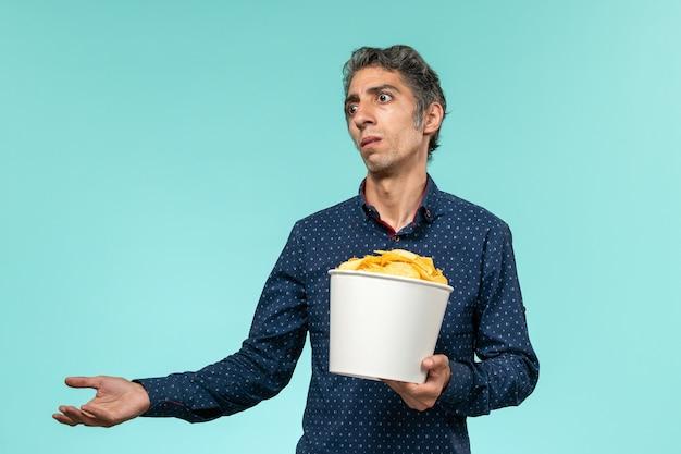 Cestino maschio di mezza età della tenuta di vista frontale con le patatine fritte sulla superficie blu
