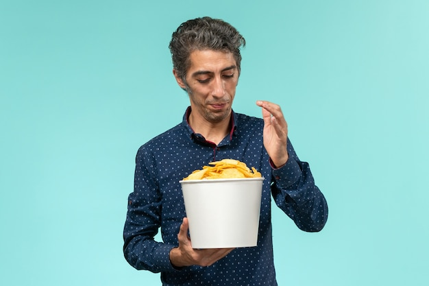 Front view middle-aged male holding basket with potato cips on the blue surface