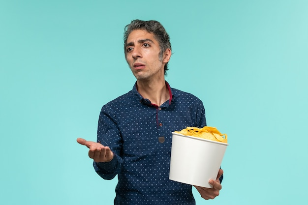 Front view middle-aged male holding basket with potato cips on light-blue surface