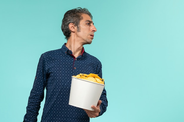 Front view middle-aged male holding basket with potato cips on the light blue surface