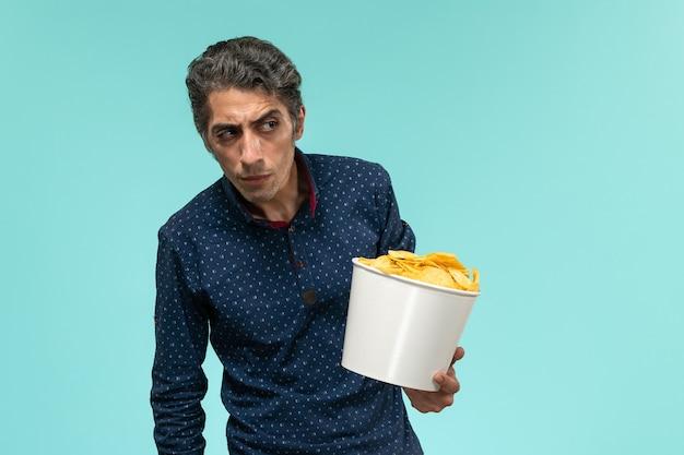 Вид спереди мужчина средних лет, держащий корзину с картофельными чипсами на синей поверхности