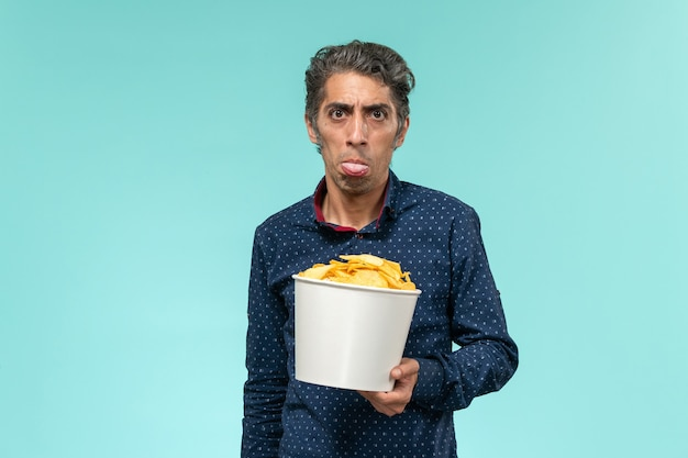 Вид спереди мужчины среднего возраста, держащего чипсы и едящего на синей поверхности