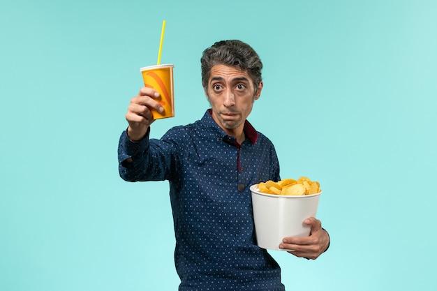ジャガイモのcipsを保持し、青い表面で飲む中年男性の正面図