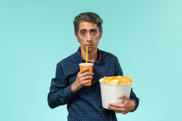 正面図中年男性がジャガイモのcipsを保持し、水色の表面で飲む