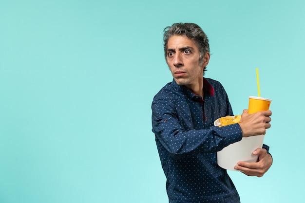 Мужчина средних лет, вид спереди, держит картофельные чипсы и газировку на синей поверхности
