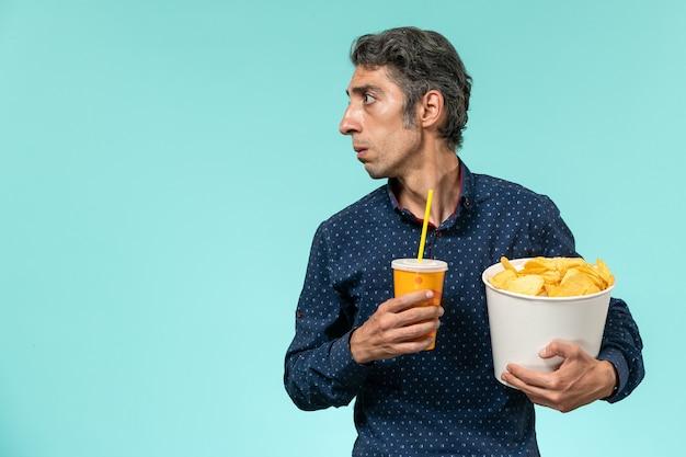 青い表面にジャガイモのcipsとソーダを保持している正面図中年男性