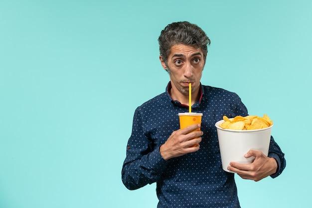 水色の表面にジャガイモのcipsとソーダを保持している正面の中年男性