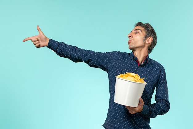 Front view middle-aged male holding potato cips on blue surface
