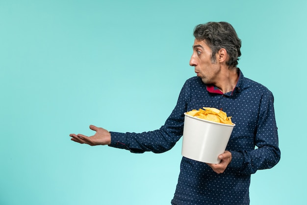 Front view middle-aged male holding potato cips on the blue surface