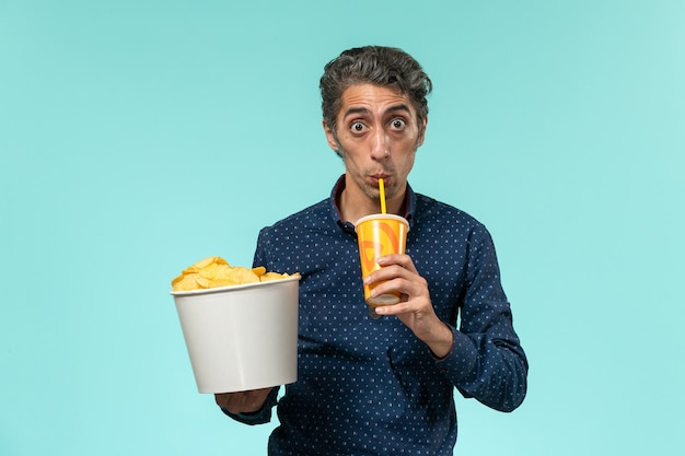 Vista frontale maschio di mezza età in possesso di patatine fritte e bere soda su una superficie blu