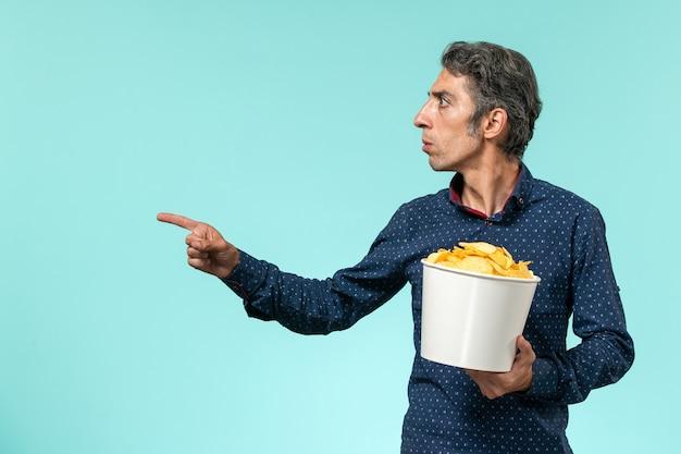 青い表面にジャガイモのcipsを保持している正面図中年男性