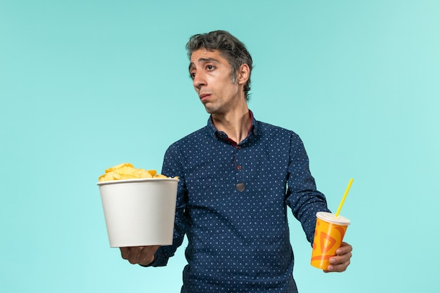Front view middle-aged male holding potato cips and soda on a blue desk