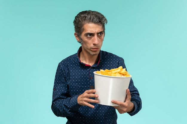 Vista frontale maschio di mezza età con cesto pieno di patatine sulla superficie blu