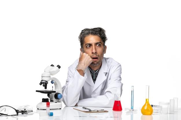 Вид спереди ученого средних лет в медицинском костюме, сидящего за столом с растворами