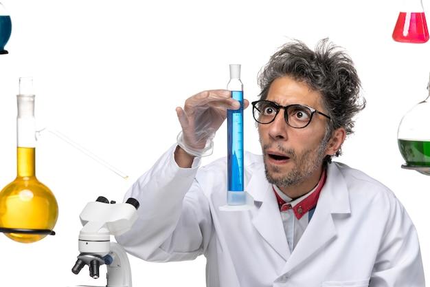 파란색 솔루션으로 작업하는 의료 소송에서 전면보기 중년 과학자