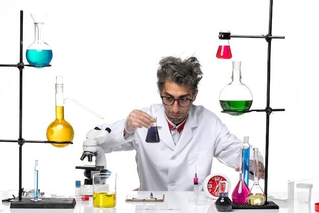解決策を扱い、混乱している医療スーツの中年の科学者の正面図
