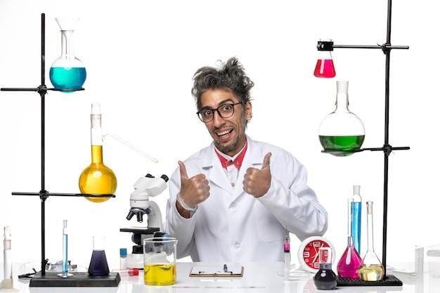 Вид спереди ученого средних лет в медицинском костюме, работающего с растворами