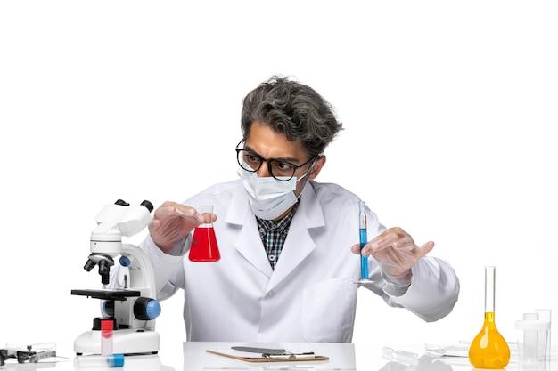 溶液の入ったフラスコを保持する特別なスーツを着た中年の科学者の正面図
