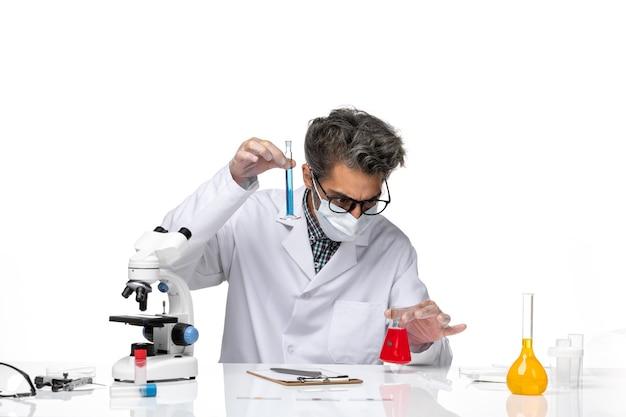解決策とフラスコを保持して座っている特別なスーツを着た中年の科学者の正面図