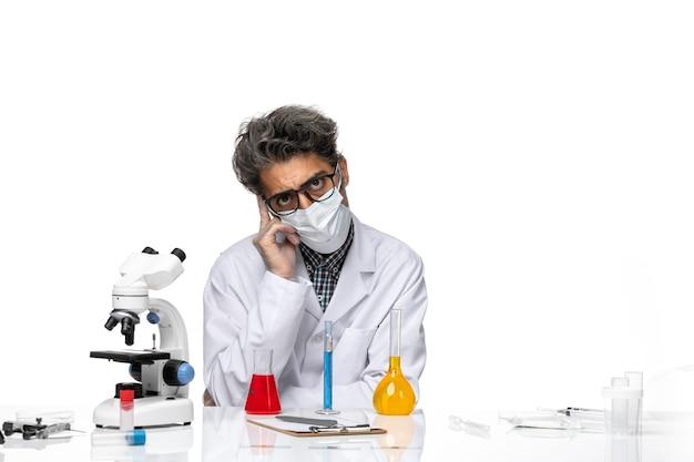 Вид спереди ученого средних лет в специальном костюме, сидящего с решениями и думая