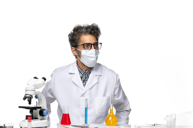 Вид спереди ученого средних лет в специальном костюме, сидящего с решениями