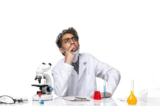 Вид спереди ученого средних лет в специальном костюме, пишущего заметки и думая