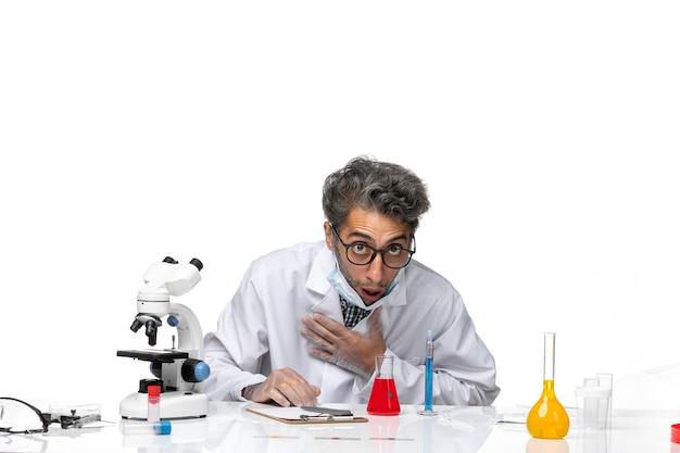 Вид спереди ученый средних лет в специальном белом костюме, пахнущий красным раствором и плохо себя чувствующий