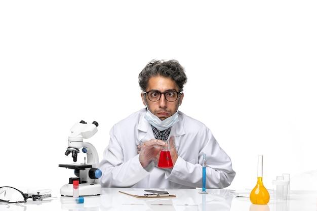 特別な白いスーツを着た中年の科学者が赤い溶液の匂いを嗅ぎ、気分が悪い正面図
