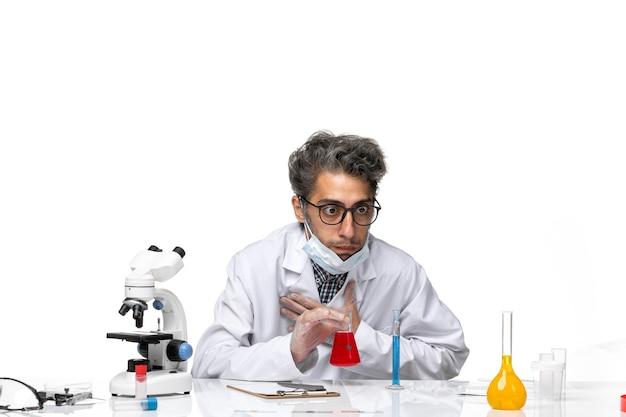 赤い解決策のにおいがする特別な白いスーツの中年の科学者の正面図