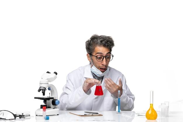 特別な白いスーツの匂いを嗅ぐソリューションの中年の科学者の正面図