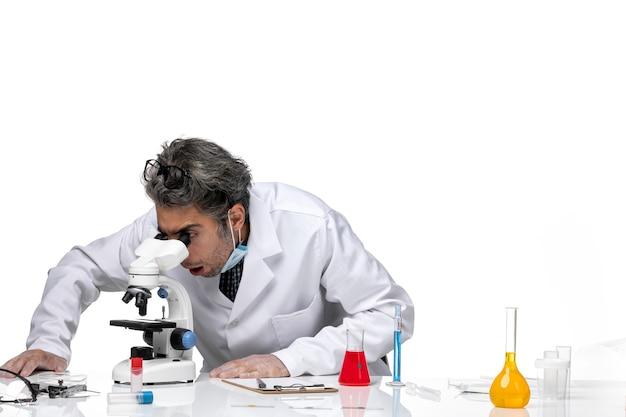 Вид спереди ученого средних лет в специальном белом костюме с помощью микроскопа
