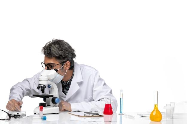 현미경을 사용하는 특수 흰색 정장의 전면보기 중년 과학자