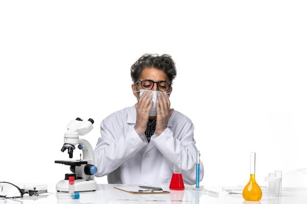 マスクを身に着けている特別な白いスーツを着た中年の科学者の正面図