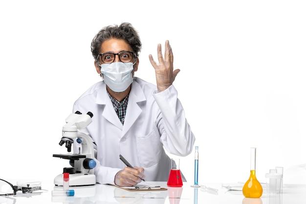 Вид спереди ученый средних лет в специальном белом костюме, пишущий заметки