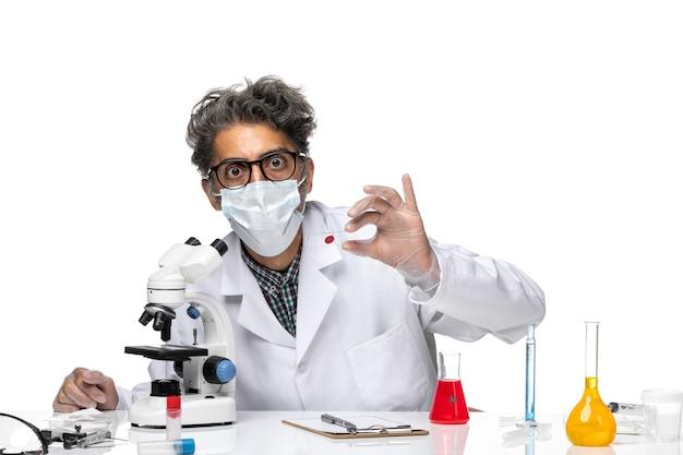 작은 샘플을 검사하는 흰색 의료 소송에서 전면보기 중년 과학자