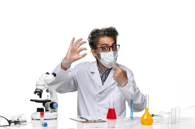 サンプルを保持している白い医療スーツの中年科学者の正面図