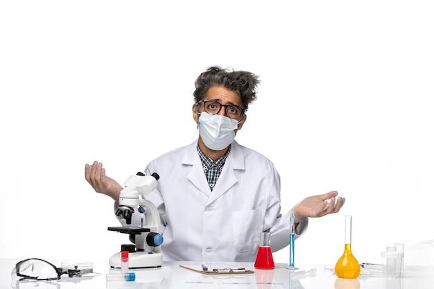 混乱した表情でポーズをとる白い医療スーツの中年科学者の正面図