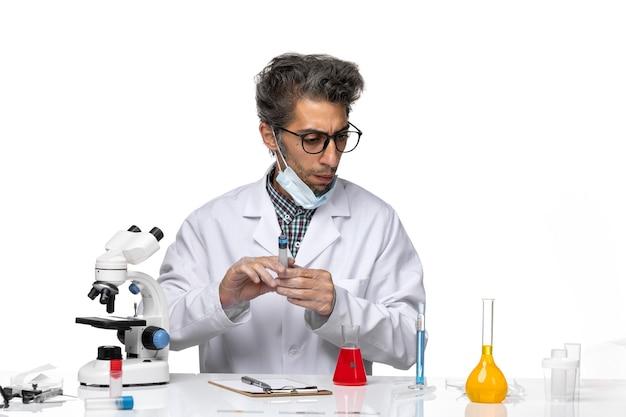 Вид спереди ученый средних лет в белом медицинском костюме готовит инъекцию