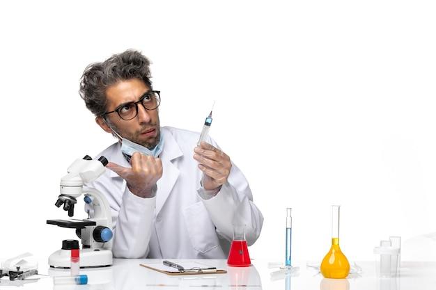 注射を準備している白い医療スーツの中年の科学者の正面図