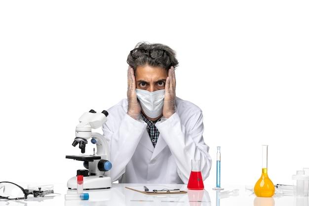 ソリューションとテーブルの周りに座っている白い医療スーツの中年科学者の正面図