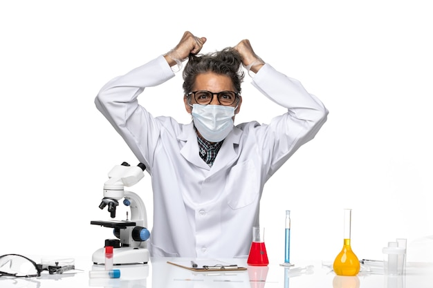 Вид спереди ученого средних лет в белом медицинском костюме рвет волосы