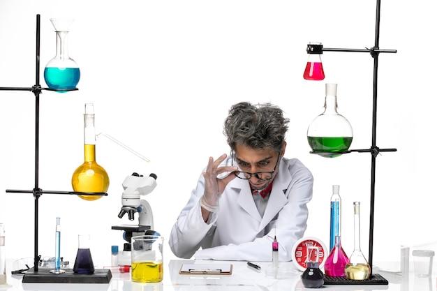 솔루션으로 작업하는 흰색 의료 소송에서 전면보기 중년 과학자