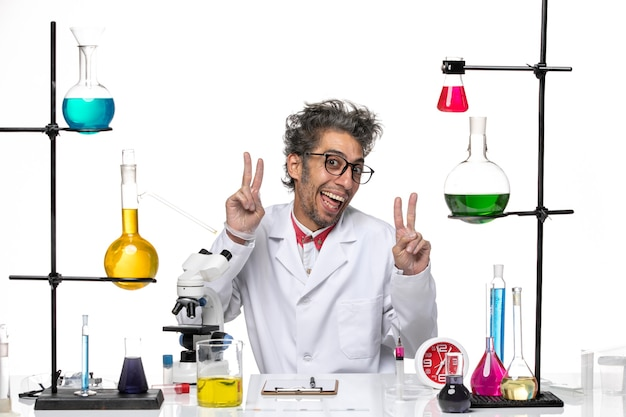 Front view middle-aged scientist in medical suit posing in funny manner