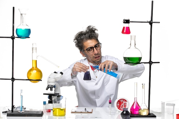 Scienziato di mezza età di vista frontale in vestito medico che lavora con le soluzioni