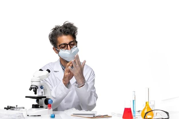 Scienziato di mezza età di vista frontale in vestito speciale con i guanti da portare della maschera