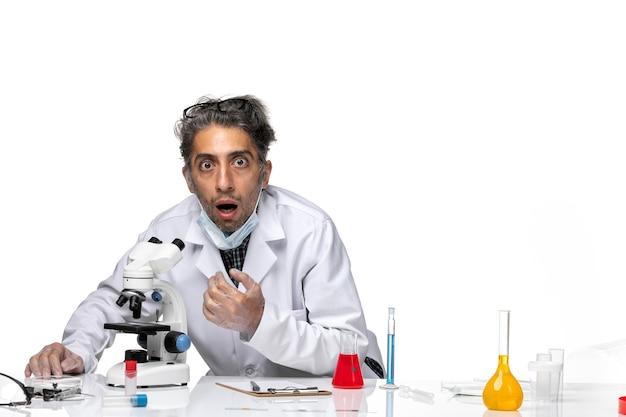 Scienziato di mezza età di vista frontale in vestito bianco speciale facendo uso del microscopio