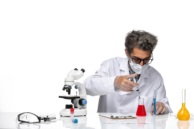 Front view middle-aged scientist in white medical suit filling injection with solution